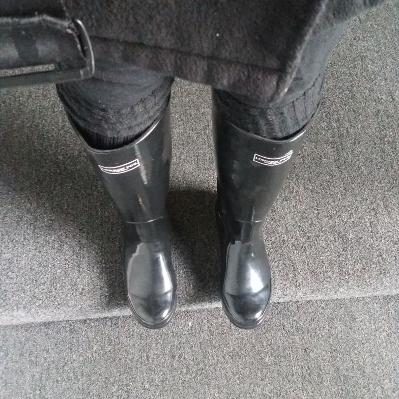 [image description: shiny black rain boots, black socks and the edge of a black coat.]