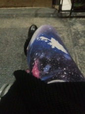 [image description: galaxy print leggings on crossed thighs with the tip of a black boot visible in the background]